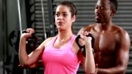 Trainer helping woman with kettlebells video