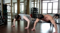 Trainer in the gym shows his thick ward how to do push-ups video