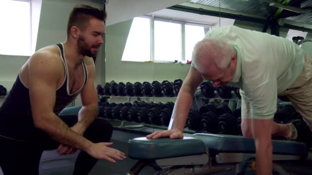 Trainer watching how senior client does exercises video
