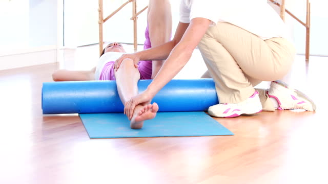 Trainer working with woman on exercise mat video