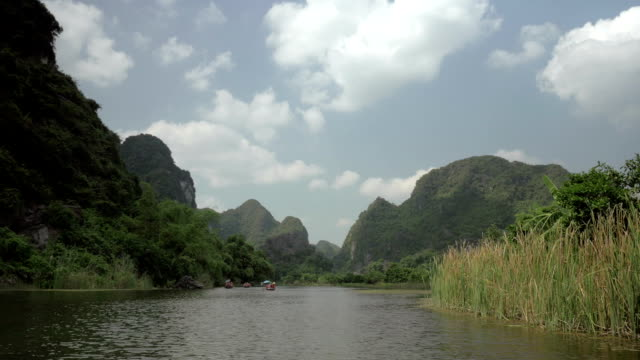 Trang an bai in Hanoi, Vietnam on a scenic river sailing boat with tourists video