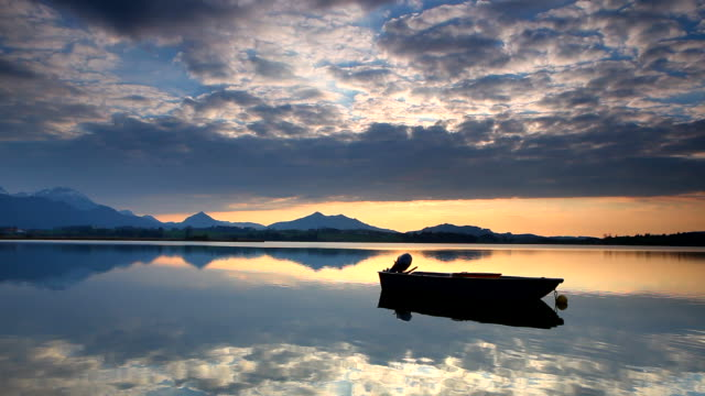 tranquil sunset at lake hopfensee, bavaria, boat, germany video
