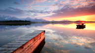 tranquil sunset at lake hopfensee, bavaria with jetty, boat, germany video