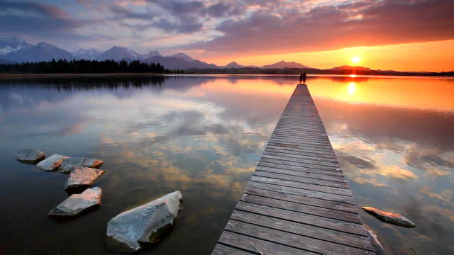 tranquil sunset at lake hopfensee in bavaria with pier- germany video