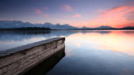 tranquil sunset at lake with jetty in bavaria - germany video