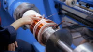 Transformer, engine production. Worker winding cooper wires on a high voltage transformer. Slider shoot video