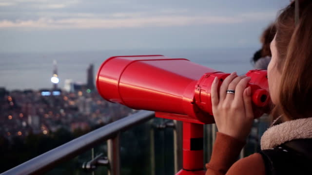 Travel: young woman tourist looking at city through coin-operated binoculars at sunset. Close-up shot, handheld, slow motion 60fps video