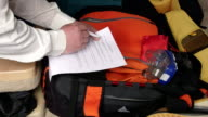Traveler packing travel bag using checklist of items to pack for summer vacation video