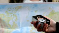 Traveler searching direction with a compass on background of map video