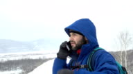 Traveler With a Beard Talking Smartphone On Mountain. Caucasian Men in Jacket looking for a GPS Signal. Mountaineer Winter Mobile Communications.Adventure Expedition Man Talk Cell Men Call Accident video