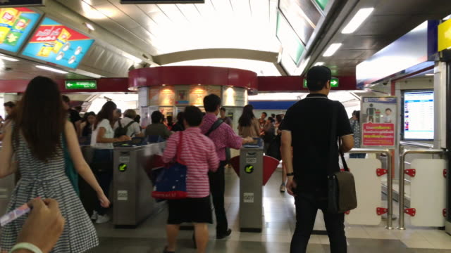 Travelers passing ticket barrier at Train Station video