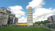 Travelers visiting famous leaning Pisa tower in Italy. Summer clouds timelapse video