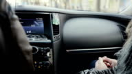 Traveling by car. Woman sitting near the driver in a fur coat with her hands on knees. Black dashboard of the car video