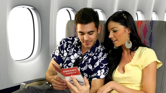Traveling Couple Reviewing An Airplane Safety Card video