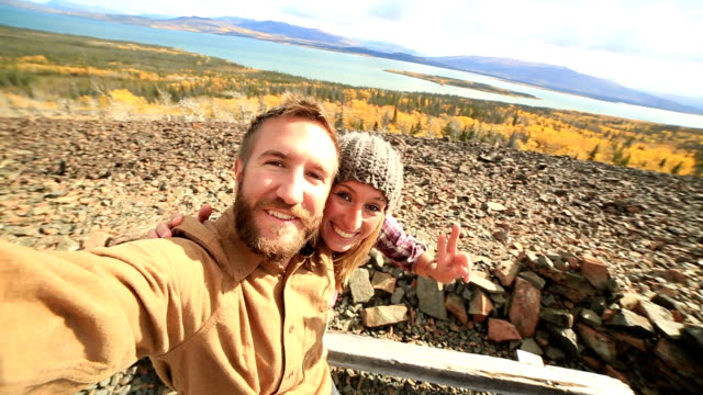 Traveling young couple taking selfie on mountain video
