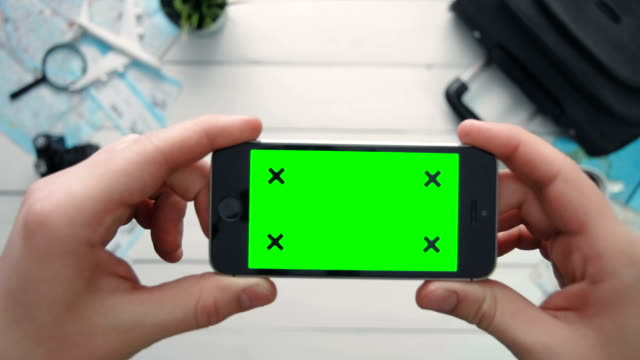Travelling concept Top view traveler's hand holding phone horizontal with green screen and tracking points at white wooden desk video