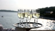 Tray glasses champagne hands waiter at sea view at sunset video