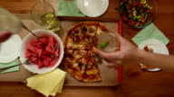 Tree glass clang, small home party with pizza and watermelon, top table view video