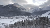 AERIAL Treetops on the hill surrounding a valley in winter video