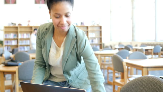 Trendy African American adult college student walks to computer in library to study video