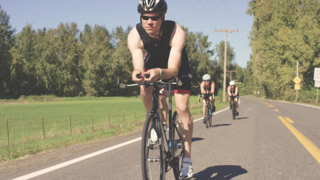 Triathletes riding bikes training for a triathlon on a country highway video