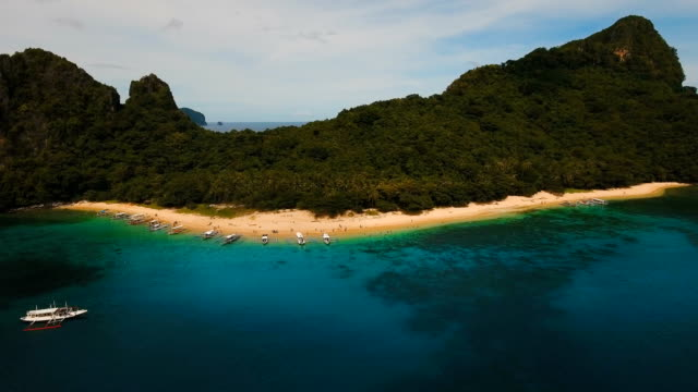 Tropical beach with boats, aerial view. Tropical island video