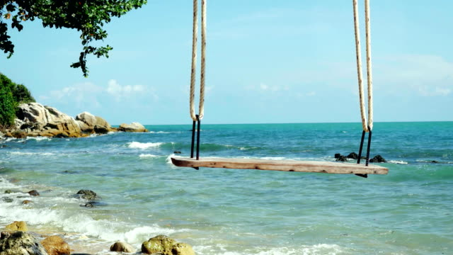 Tropical Island Beach and Tree Swing. Splashing waves in the Sea at stones on beautiful background on the blue sky. Paradise at Koh Samui. 3840x2160 video
