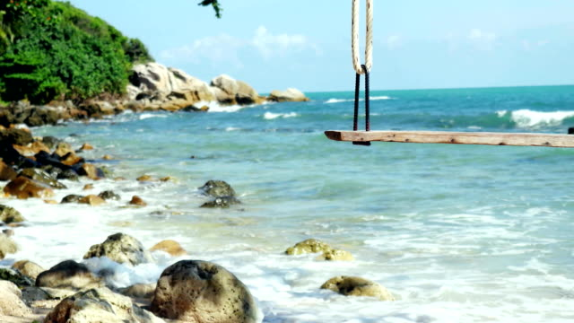 Tropical Island Beach and Tree Swing. Splashing waves in the Sea at stones on beautiful background on the blue sky. Paradise at Koh Samui. FullHD video