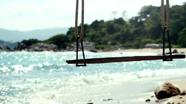 Tropical Island Beach and Tree Swing. Splashing waves in the Sea at stones on beautiful background on the blue sky. Paradise at Koh Samui, 3840x2160, FullHD video