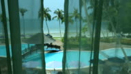 Tropical resort pool seen through room's window video
