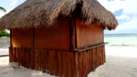 Tropical wooden hut with palm leafs roof on  sea shore video