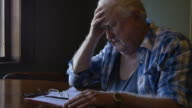 Troubled elderly man with head in hands looking sad and stressed video
