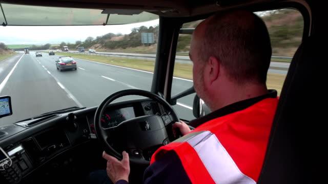 Truck Driver sat behind the steering wheel driving video