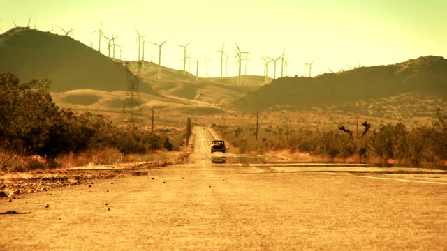 Truck Driving Down Desert Road from Wind Farm video