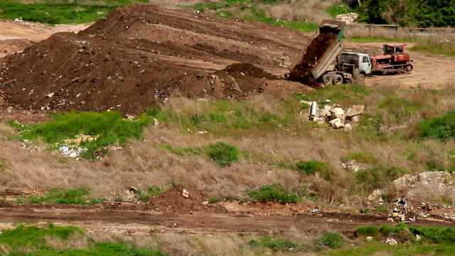 Truck unloads land and bulldozer is leveling embankment video