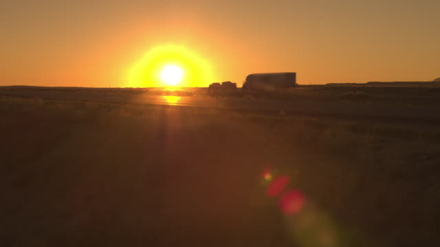 AERIAL: Trucks and cars traveling across vast plain countryside road at dawn video