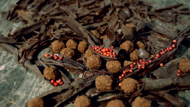truffles in dark chocolate with red pepper and chocolate chips. video