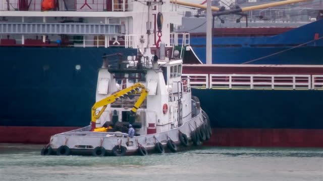 Tug assisting ship in mooring operations video