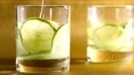 Tumbler with lemon slices pour sparkling water. video