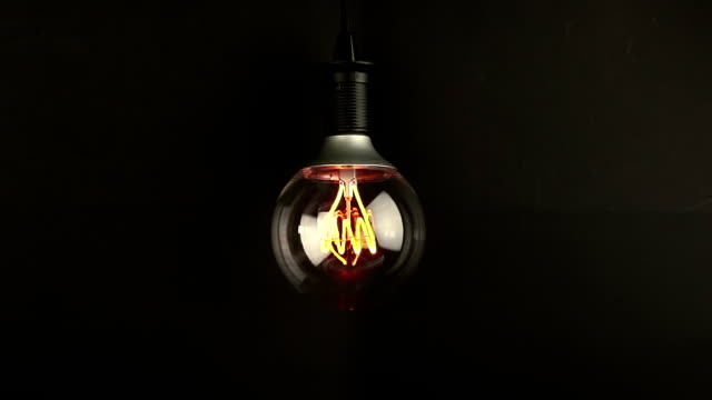 turn on and turn off, with blinking effect, retro vintage light bulb with led technology built-in on warm light yellow tint and black background, energy saving with old style atmosphere video