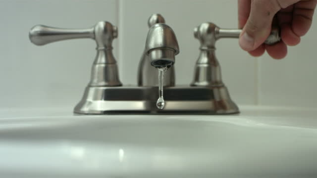 Turning on faucet, slow motion video