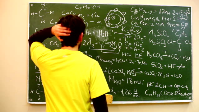 Tutor explaining something to a student at the blackboard video