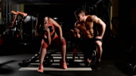 tutorship. Gym woman push-up strength pushup with dumbbell in a fitness workout. encourages her comrade video