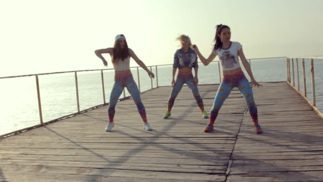 Twerk by young energetic teen girls on a wooden pier near the sea video