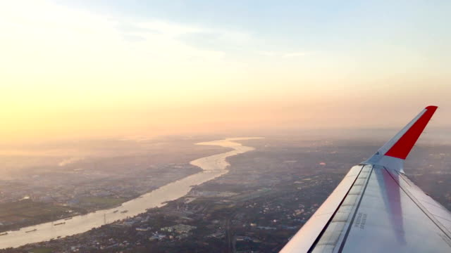 twilight sky with city and river view from window seat on airplane video