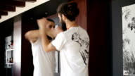 Twin brothers practice in Chinese martial arts in the training hall video