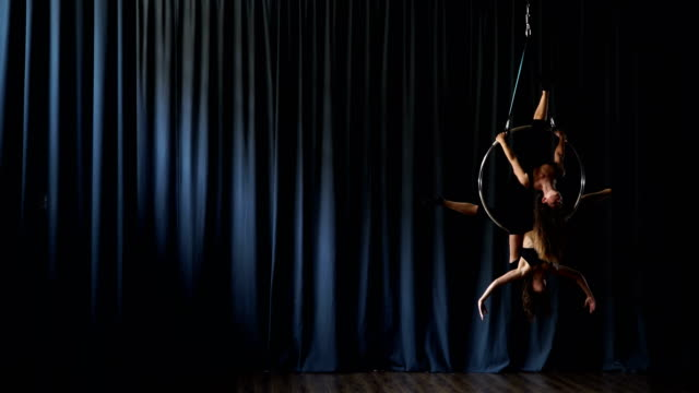 Two acrobats performs a gymnastic element on the aerial trick video