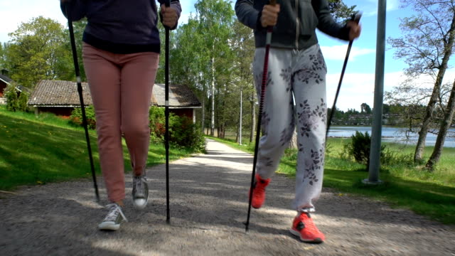 Two active women do Nordic walking in the Park. Tracking shot. Slow Motion video