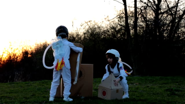 Two adorable children, boy brothers, playing in park on sunset, dressed like astronauts, imagining they are flying on the moon video