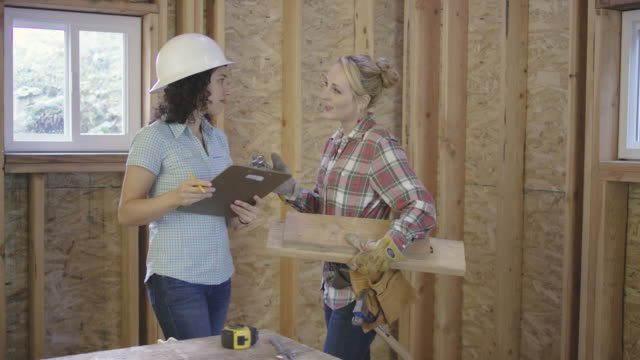 Two adult females discussing home diy building project video